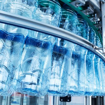 Closeup Water bottling line for processing and bottling pure mineral carbonated water into bottles and gallons.